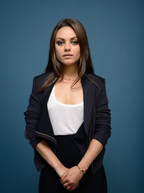 Mila Kunis in a white t-shirt and blue blazer