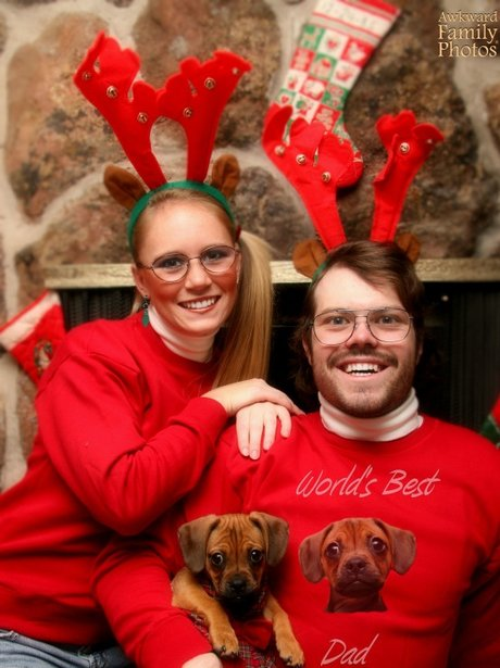 A man and a woman in red jumpers with their dog