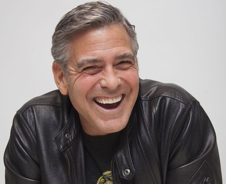 George Clooney laughing in a black leather jacket at press junket