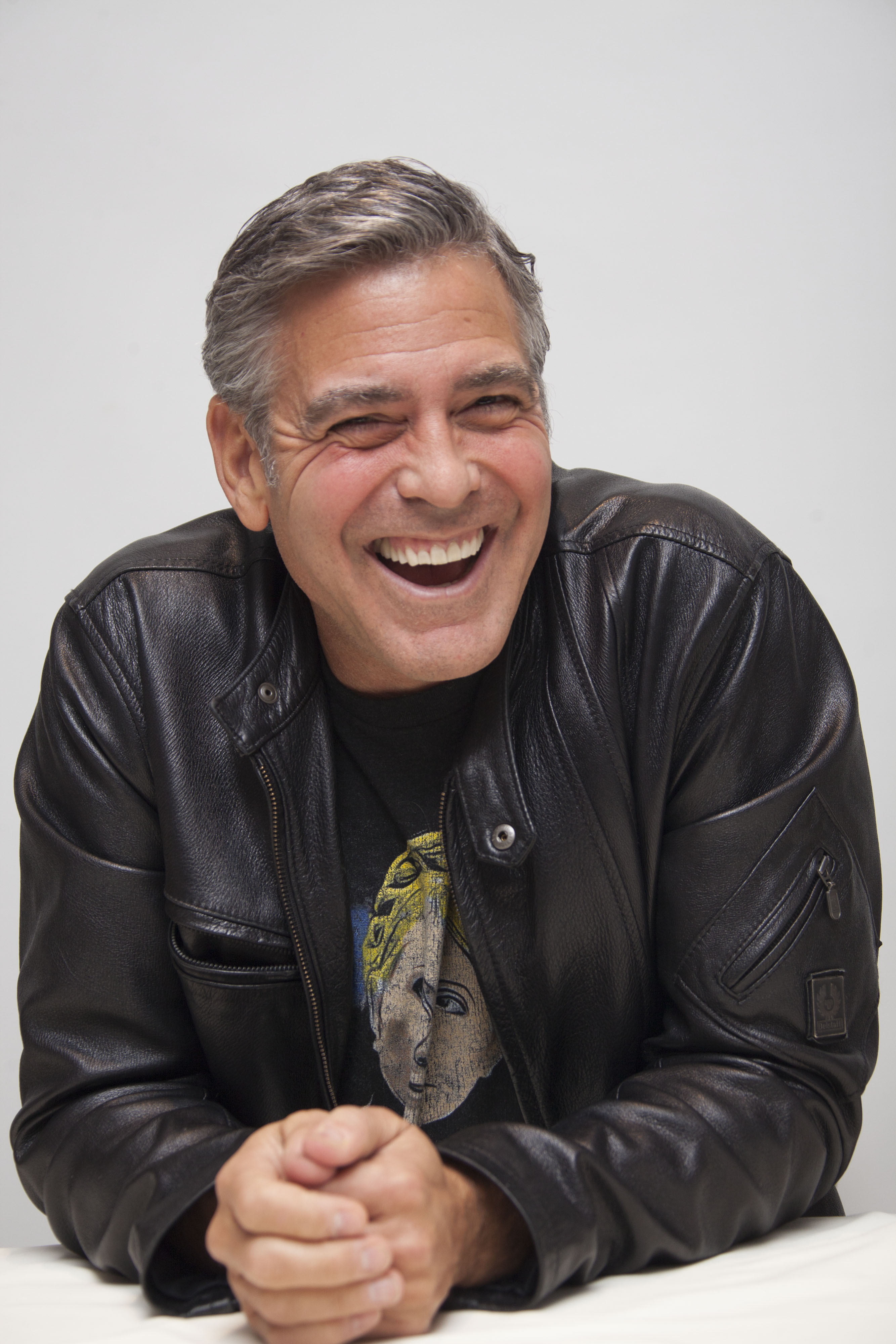 Clooney laughing in a black leather jacket