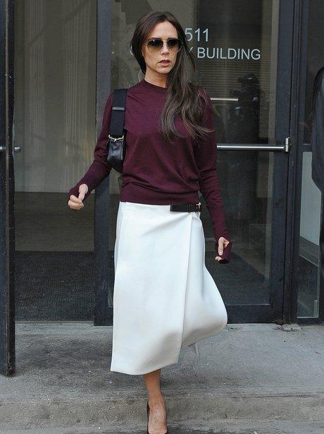 Victoria Beckham in purple jumper and white skirt