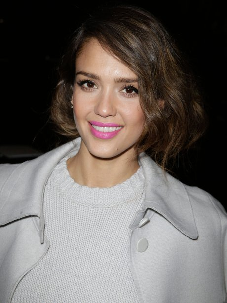 Jesica Alba wearing bright pink lipstick and a white coat and jumper