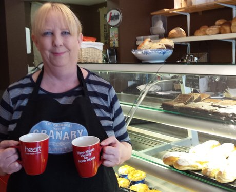 Lady holding two mugs.