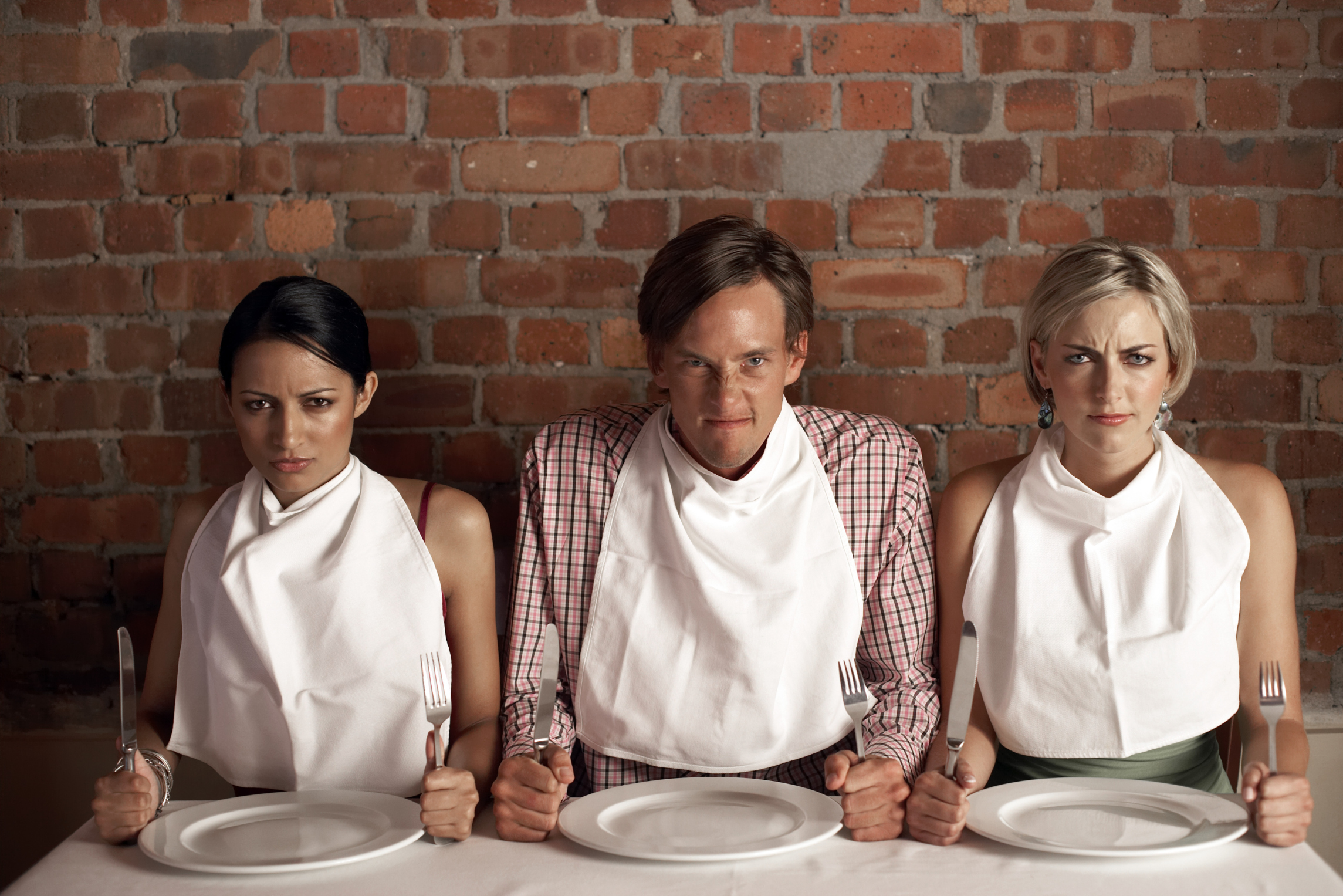 Three people wearing napkins around their necks