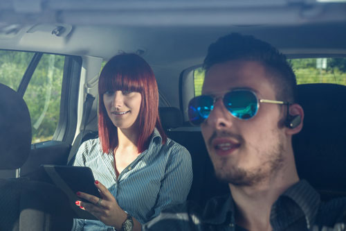 Man wearing bluetooth headset with woman in car