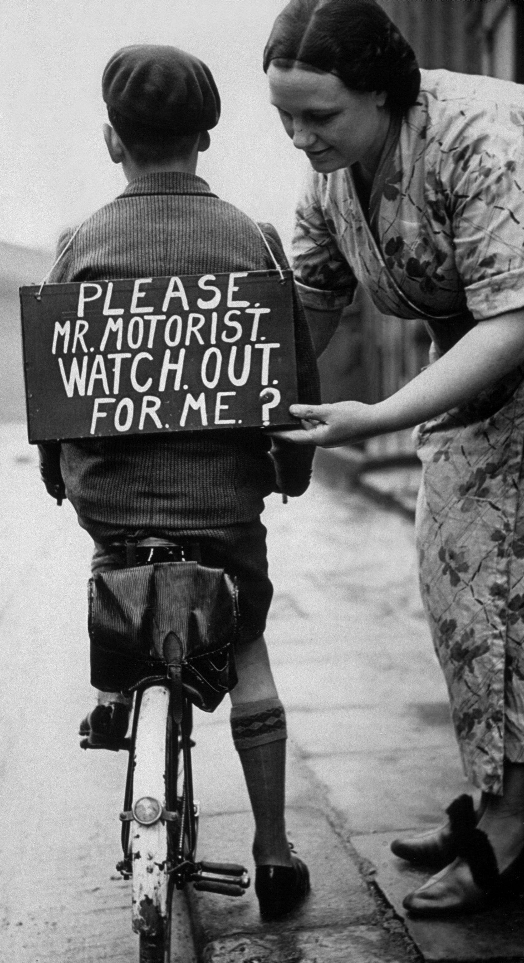A mother fastening a notice reading 'Please Mr Mot