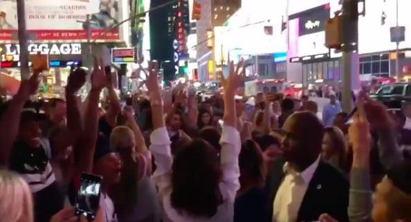 Victoria Beckham jumping in a crowd in Time Square