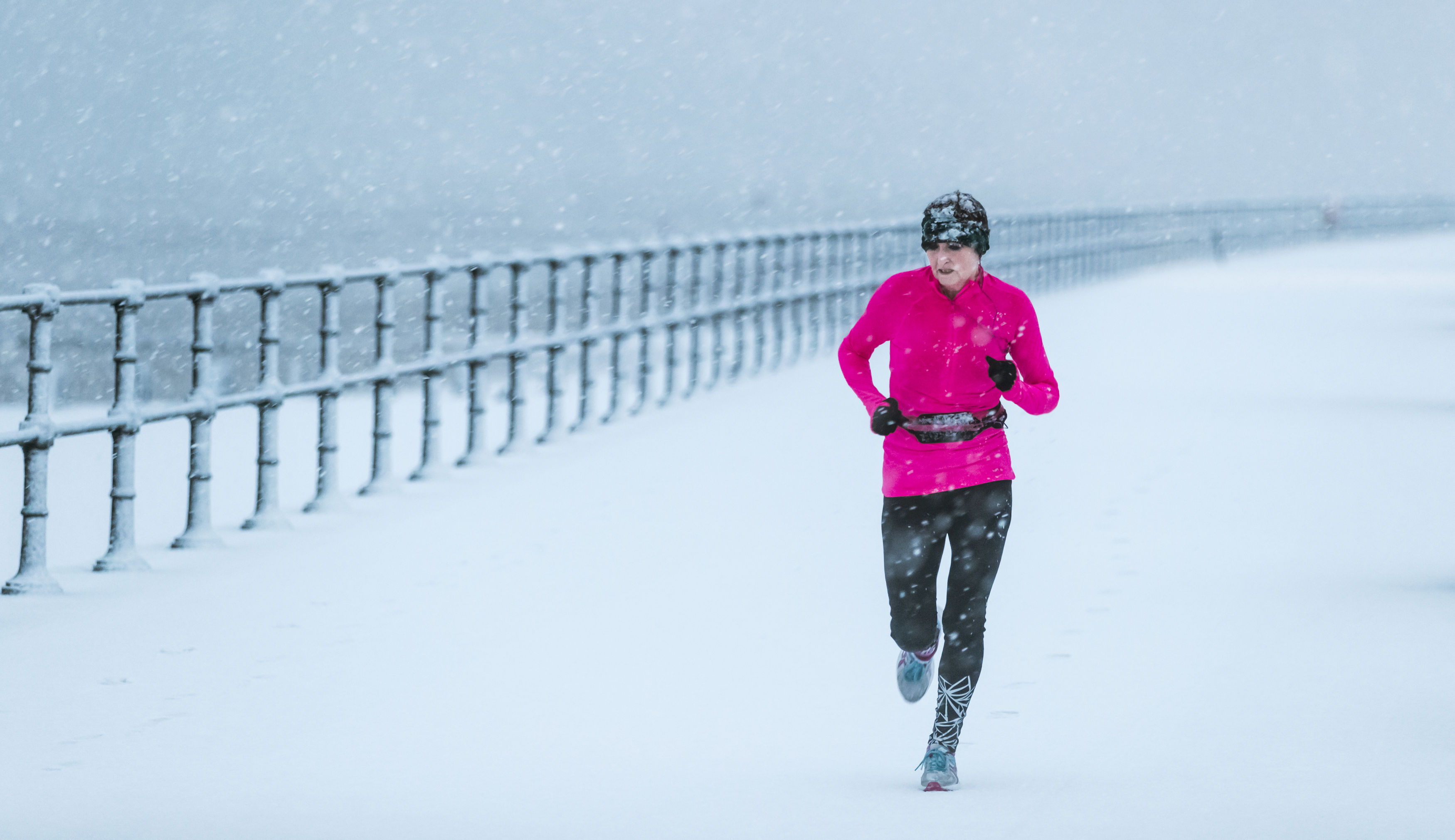 woman running in the snow Cleethorpes, Lincolnshir