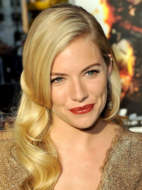 Sienna Miller with blonde curls and red lipstick