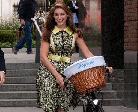Kelly Brook wears a flowery dress while riding a bike