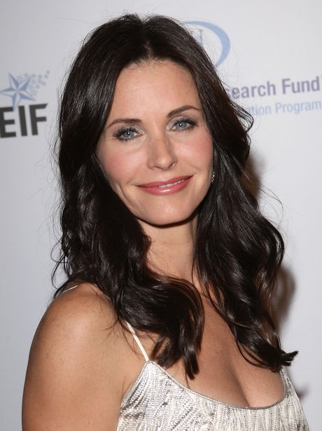 Courtney Cox in a white dress, smiling on the red carpet