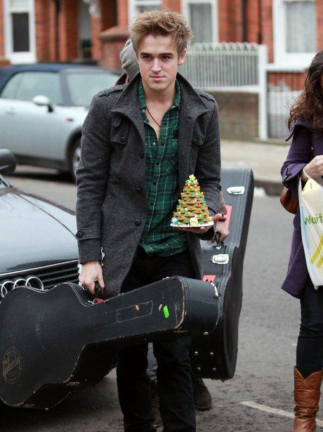 Tom Fletcher carrying a guitar case