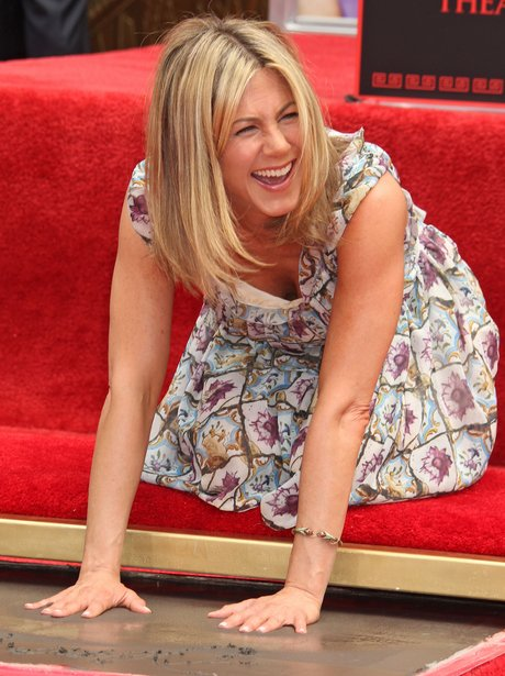 jennifer aniston in a floral dress on the hollywood walk of fame