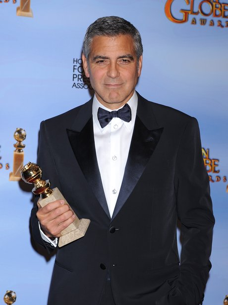 George Clooney looks handsome in a tuxedo and bow tie whilst holdin an award