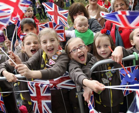 Crowds waves flags to welcome HMQ