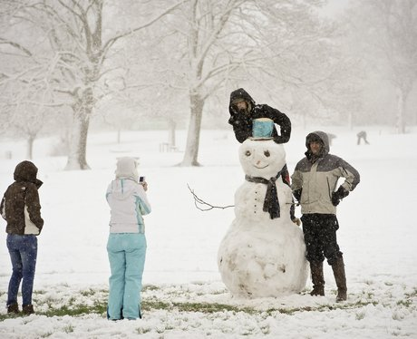 People build a snowman in a park in Bristol