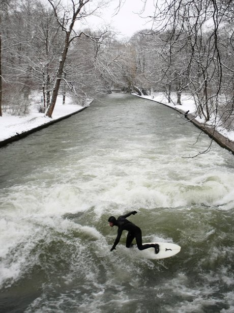 Surfer rides a wave on a river in Munich