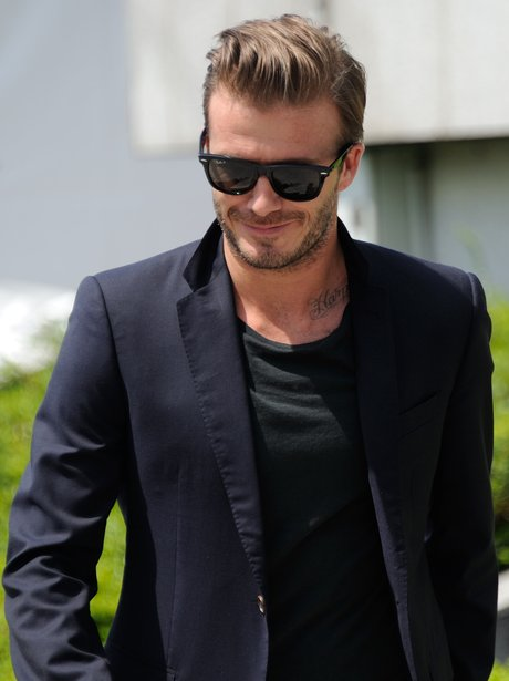 David Beckham walking wearing suit and sunglasses