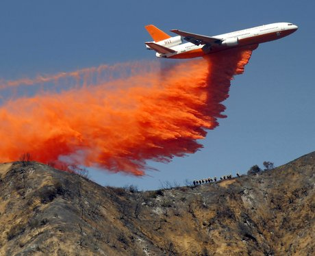 A plane drops fire retardant on a wildfire