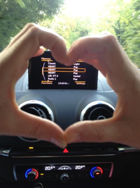 Heart hands around a car radio
