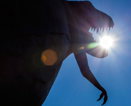 The sun behind a dinosaur statue