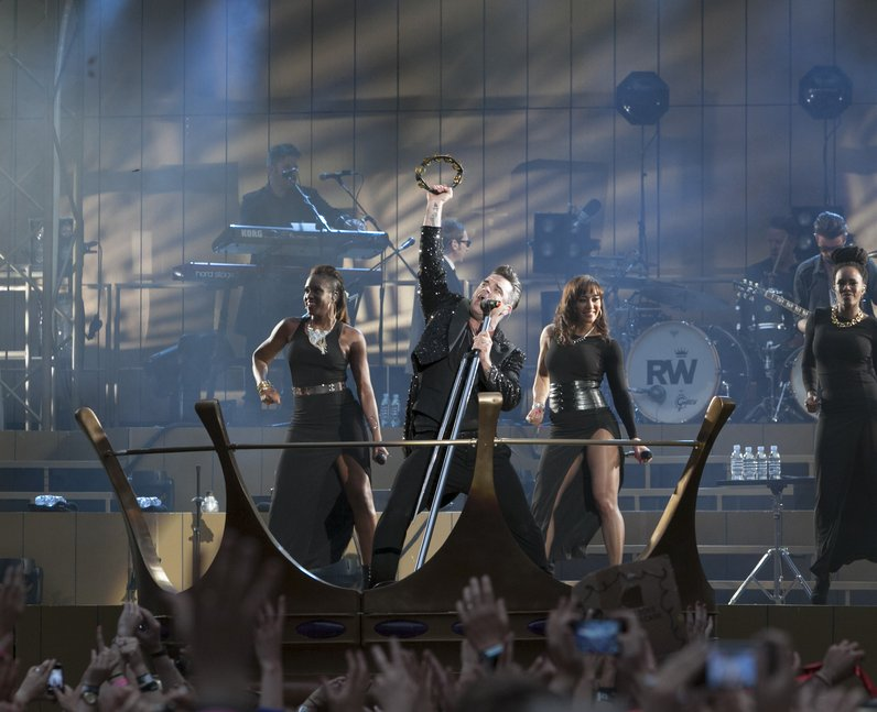 Robbie Williams shakes tambourine on stage during stadium show 2013