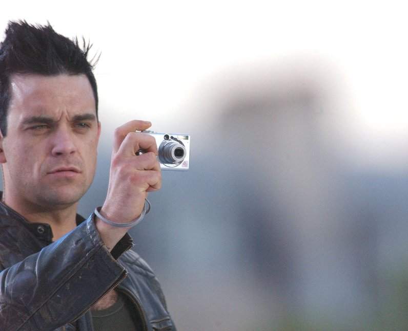 Robbie Williams on stage taking a photograph of audience