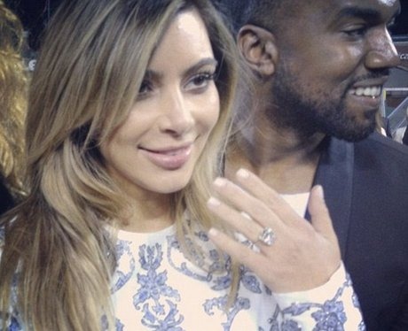 Kim Kardashian flashes her sparkling engagement ring.