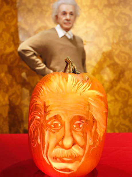 A wax figure of Albert Einstein with a pumpkin carving of his face