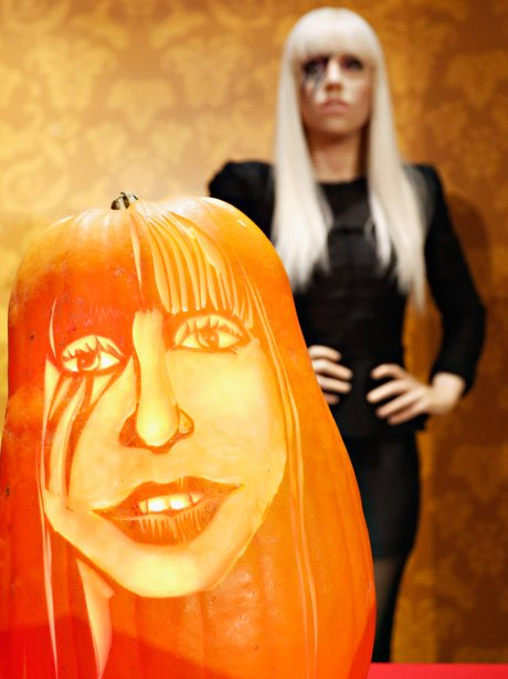 A wax figure of Lady Gaga with a pumpkin carving of her face