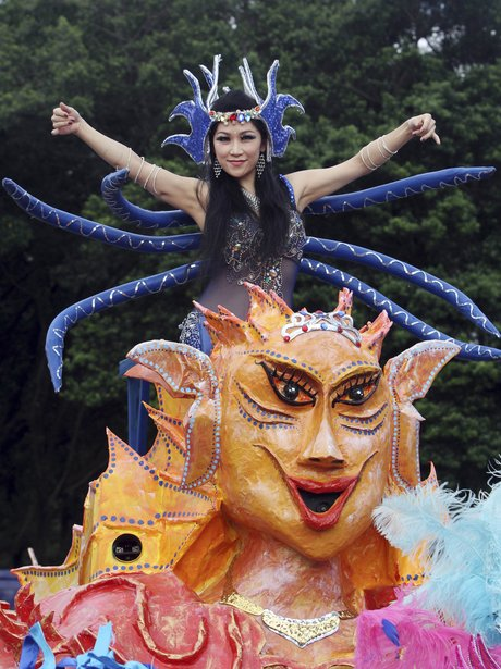 A woman in costume sits atop a float