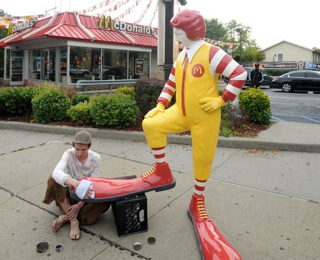 A Ronald McDonald statue getting his shoes shined