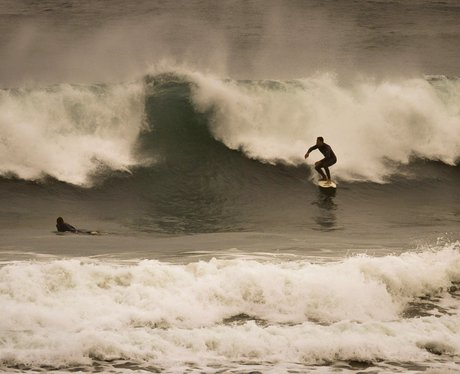 surfer rides a wave in cornwall