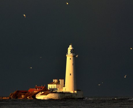 black clouds over a lighthouse
