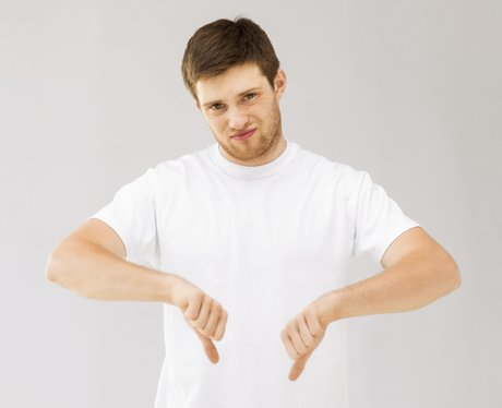 man in white t-shirt with his thumbs down