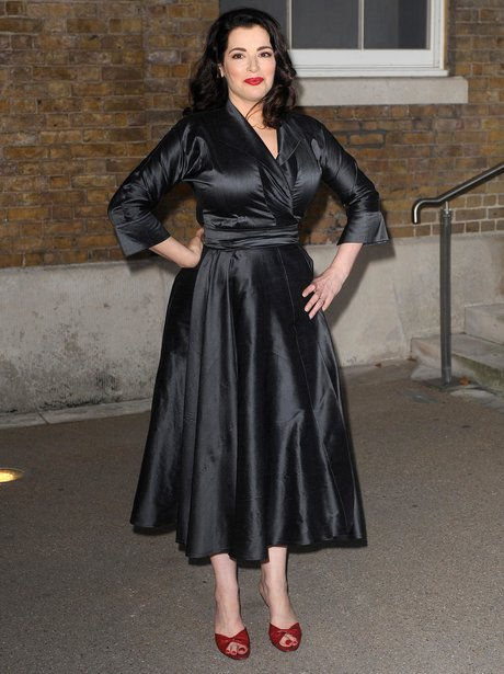 Nigella Lawson in silk black wrap dress and red heels