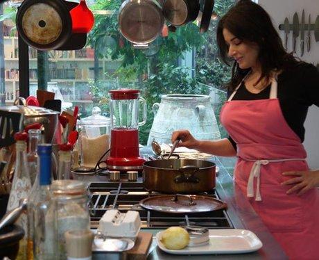 Nigella Lawson wearing a pink pinny while cooking