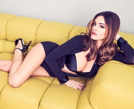 Kelly Brook wears lingerie and poses on sofa
