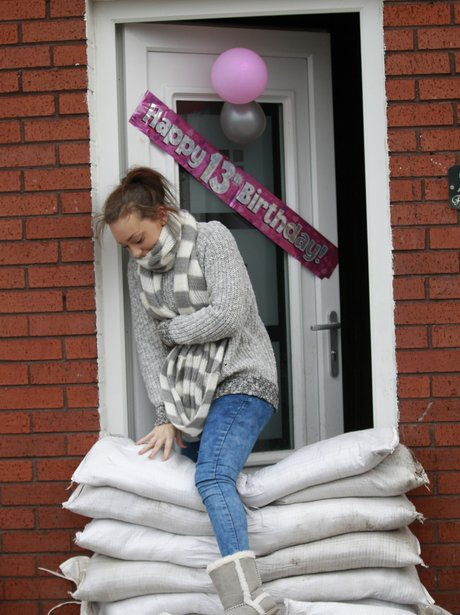 A woman climbing over sand bags outside her house.