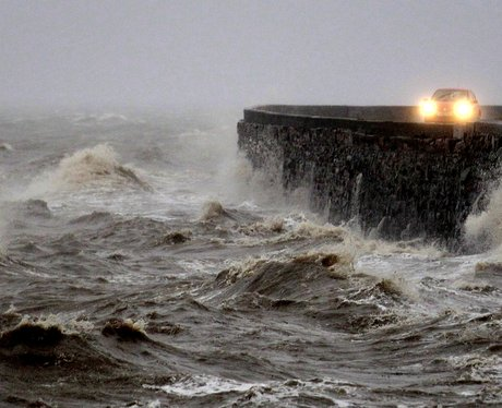 Waves battering flood defences.