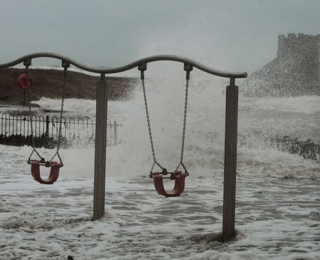 Some abandoned swings in a flooded park.