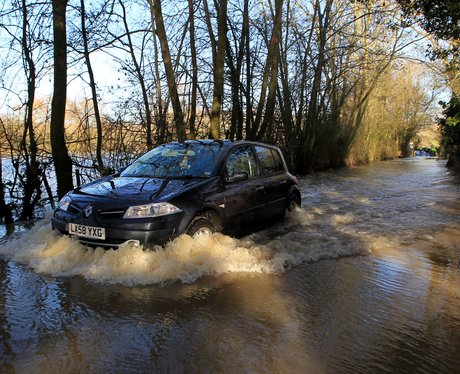 A car driving though a flooded woodland.