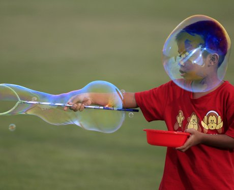 A boy creating huge bubbles with a toy