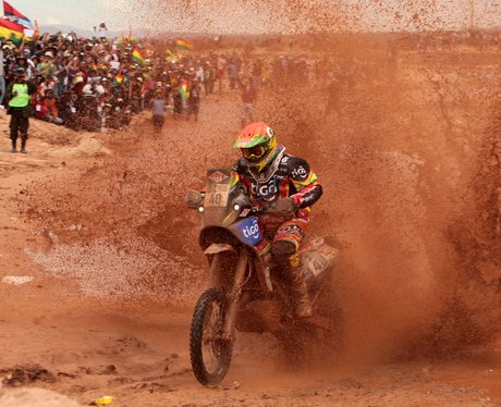 A man riding a motorbike though mud