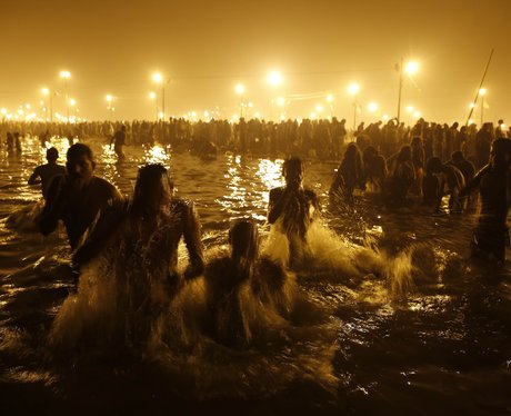 People gathered in a lake surrounded by candles