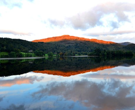 The sun rises over a lake in The Lake District
