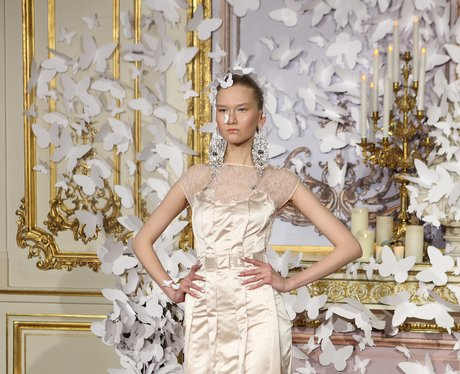 A model in a white dress surrounded by white paper butterfies