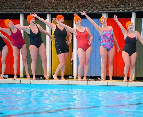 Women posing in orange hats by a swimming pool