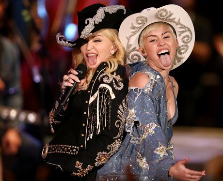 Miley Cyrus and Madonna posing as cowgirls on stage