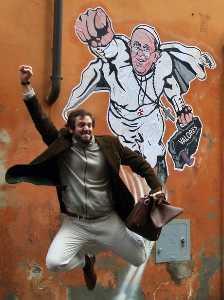 man in front of graffiti of pope